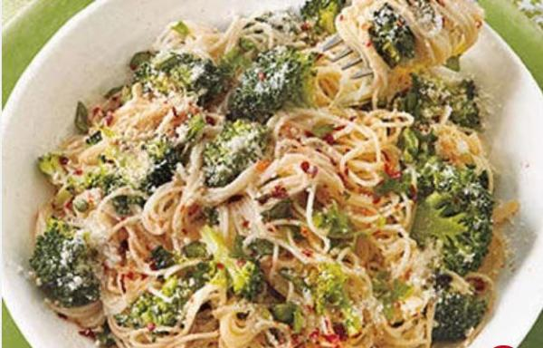 A bowl of angel-hair pasta is mixed with broccoli and Parmesan cheese.