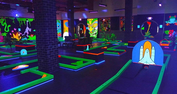 Neon and black light illuminate the mini golf course at GlowGolf
