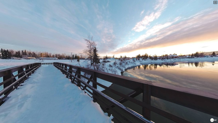 a panoramic view from a snow-covered pedestrian bridge over a river with a sunset colored sky