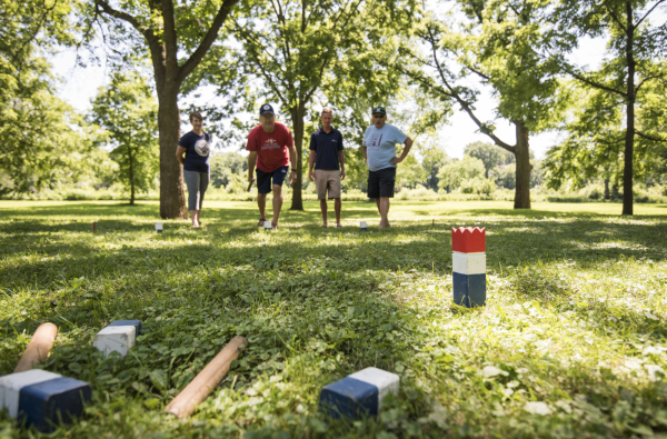 Group playing kubb in an open area