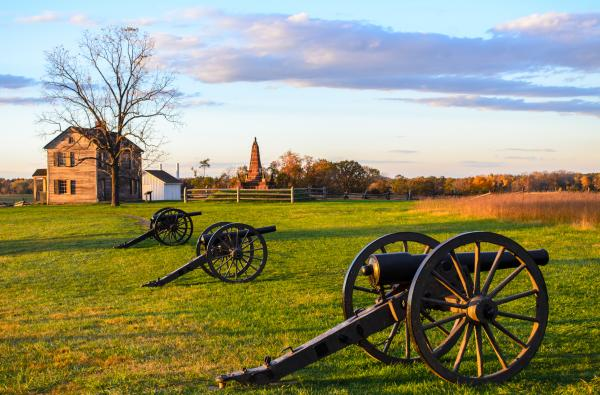 Three cannons on a battlefield with a historic house in the background