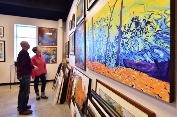 Couple admiring paintings at Artisan Forge