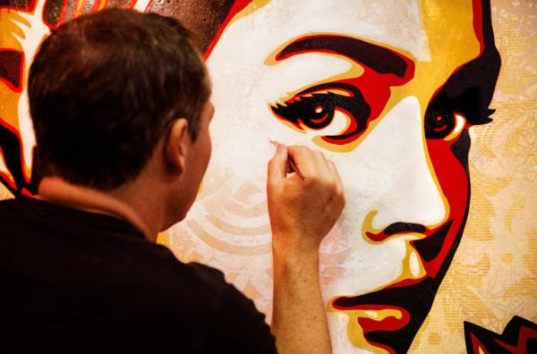 Shepard Fairey creating a wall mural of a beautiful woman