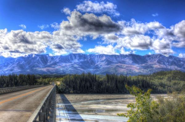 scenic view of a highway bridge over a river in summer with mountains in background