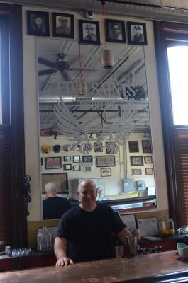 John Robert George stands beneath photos of the Five Saints