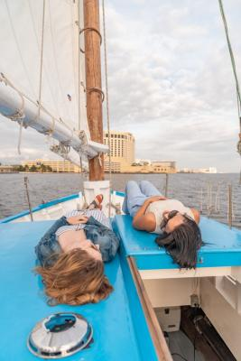 Two women laying on the deck of a boat sitting in the water.