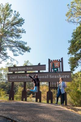 Two women posing outside in front of a sign surrounded by trees.