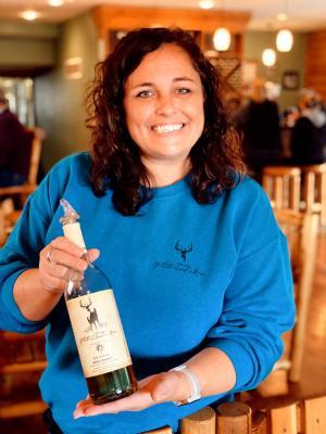 Christy Flyntz Holding a Bottle of White Tail Wine in Edgerton, KS