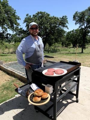 Chef Drew Curren of 24 Diner cooking hamburgers at the grill in Austin TExas