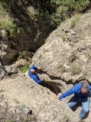 Two men climb up through a small, sandstone ravine near Albin, Wyoming.