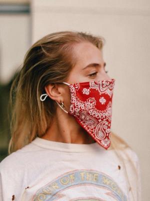 Woman models a red bandana-style medical mask.