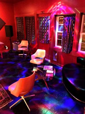 View of retro furniture and psychedelic, colorful lights inside The Oracle bar