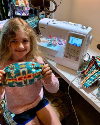 Young girl sits next to a sewing machine and displays a mask she made from Native American themed fabric.