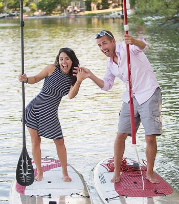 A couple poses on paddle boards on the water as an engagement
