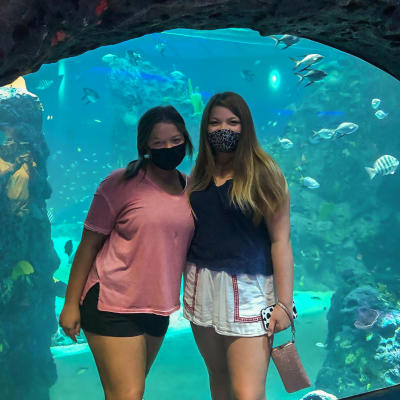 Two young ladies wearing masks and posing for a photo in front of an aquarium