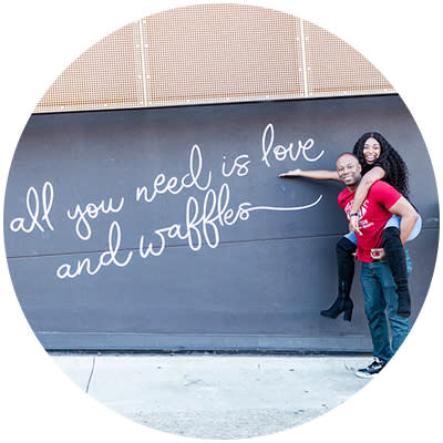 "Couple posing in front of ""All you need is love and waffles"" mural at Oklahoma City's Waffle Champion"