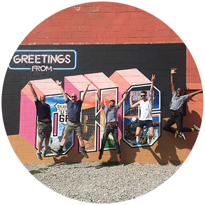 "Group of men posing in front of ""Greetings from OKC"" mural in Oklahoma City's Midtown"
