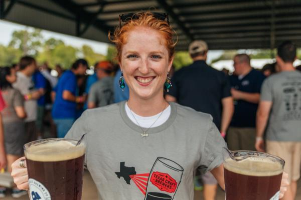 Volunteer with two pitchers of beer at Texas Craft Brewers Festival