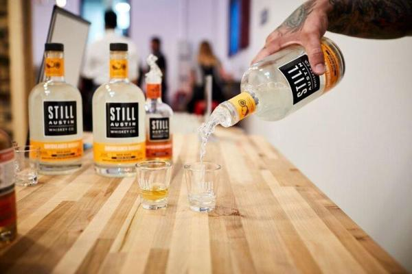 Pouring shot from bottle of Still Austin Whiskey Co