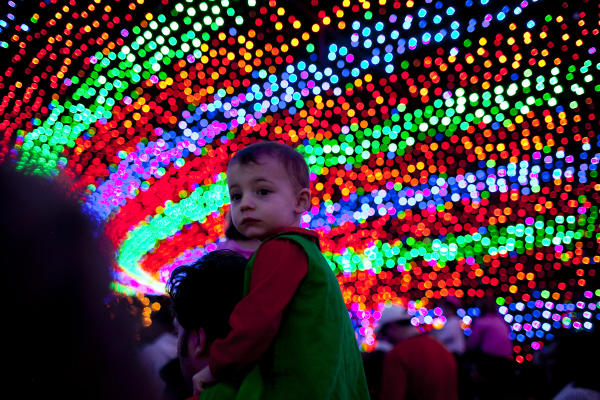 Child on adults shoulders in the tunnel of lights