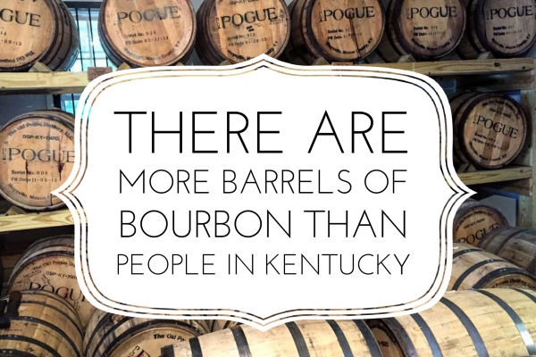 Bourbon barrels with a white sign that reads there are more barrels of bourbon than people in Kentucky.