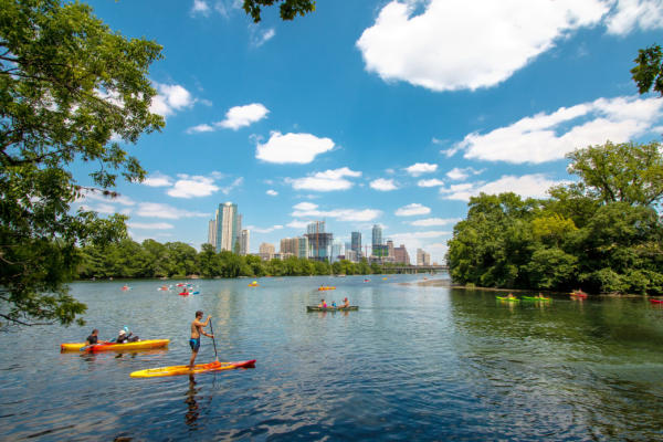 People kayaking and paddle boarding on lady bird lake near downtown Austin Texas