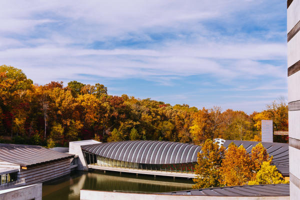 Exterior image of Crystal Bridges Museum of American Art with fall leaves surrounding the museum
