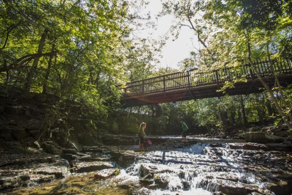 Two kids playing under a bridge in the water at Indian Run Falls.