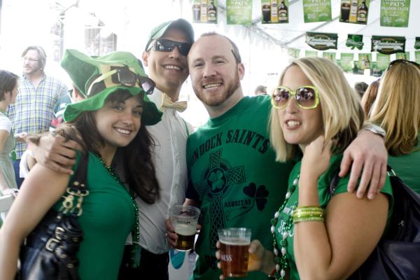 A group of people dressed for St. Patrick's Day at a tented party.
