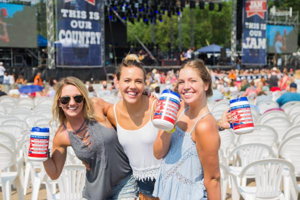 A group of 3 posing with their Country Jam bottles at Country Jam