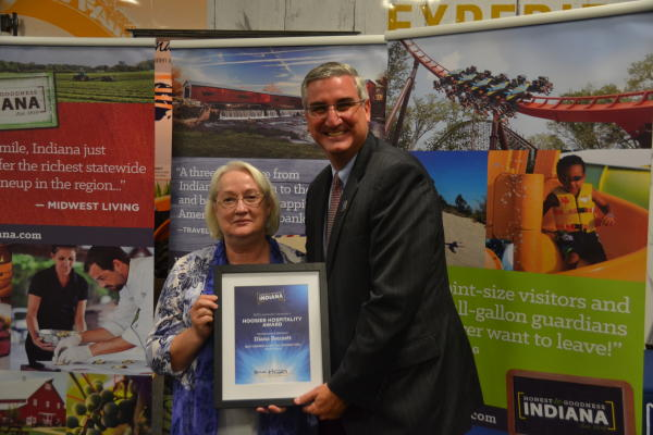 Diana Bennett (left) receives a Hoosier Hospitality Award from Indiana Lt. Gov. Eric Holcomb.