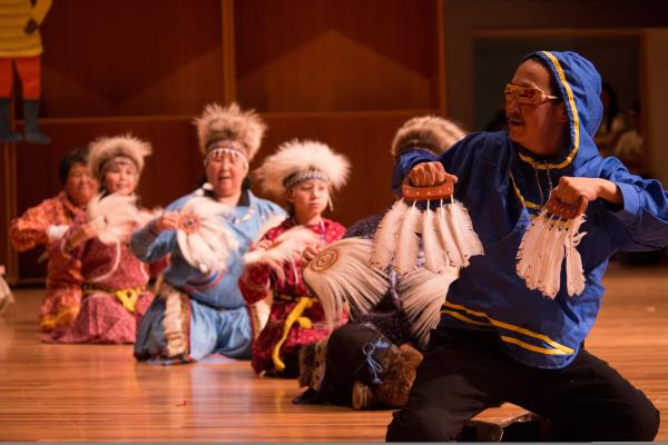 Alaska Native man and women dancing in traditional costumes