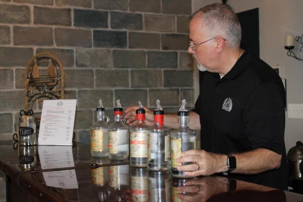 Bartender with bottles of liquor at Dragon Distillery