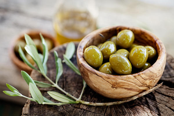 oA bowl of green olives sit in a small olive-wood bowl, next to an olive branch.