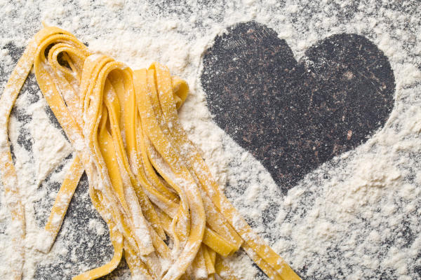 A pile of fresh-made pasta sits on a flour-dusted counter with a heart shaped clearing.