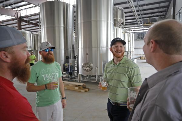 Image of men laughing & holding beer at Tall City Brewing Company.