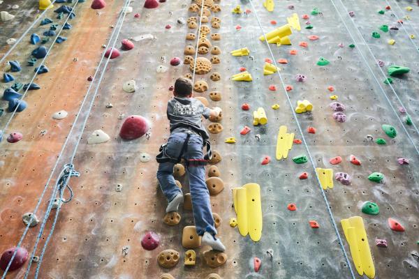Boy climbing up a rock climbing wall