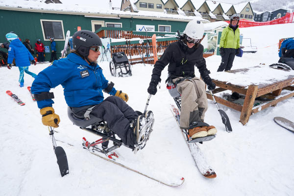 an instructor giving an adaptive ski lesson