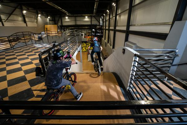 BMX biker is going down a ramp indoors