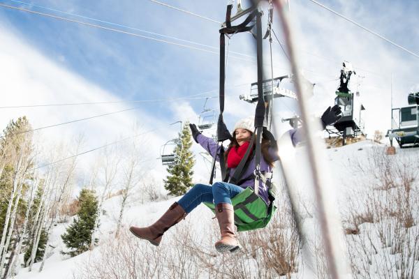 Woman sliding down zipline in winter at Utah Olympic Park