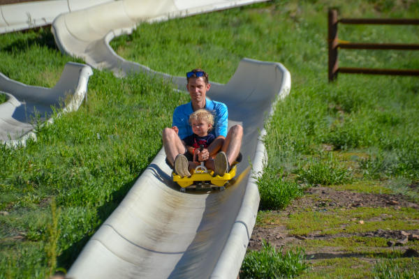 Father and Son ride down alpine slide together