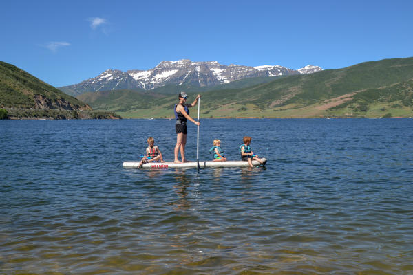 Father Stand up paddle-boarding with three kids