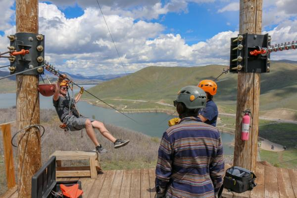 three people with helmets on top of zip line tower