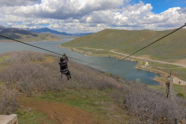 Person riding Zip Line over a lake