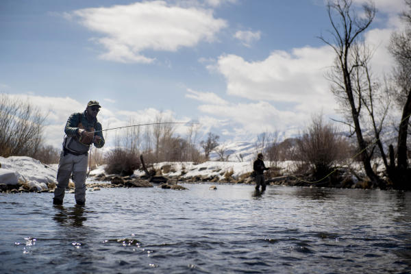 Two people fly fishing in the winter