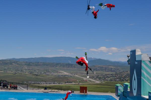 Freestyle Skiers jumping into a pool