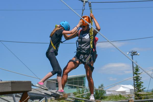 Young Girl gets assistance from adult crossing ropes course