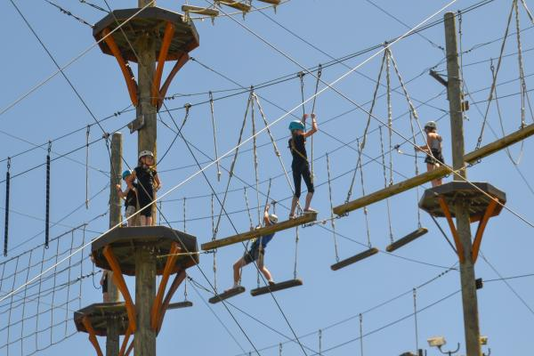 Multiple kids attempting to cross a ropes course