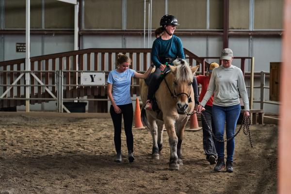 Girl riding a horse with guides walking next to horse