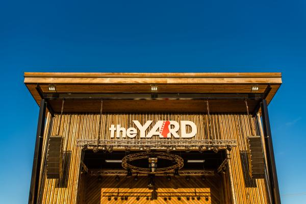 """a structure with the words """"the yard"""" on a sign on the front. This structure is used as a stage for outdoor concerts."""